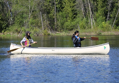 girls paddle canoe on Lake St George