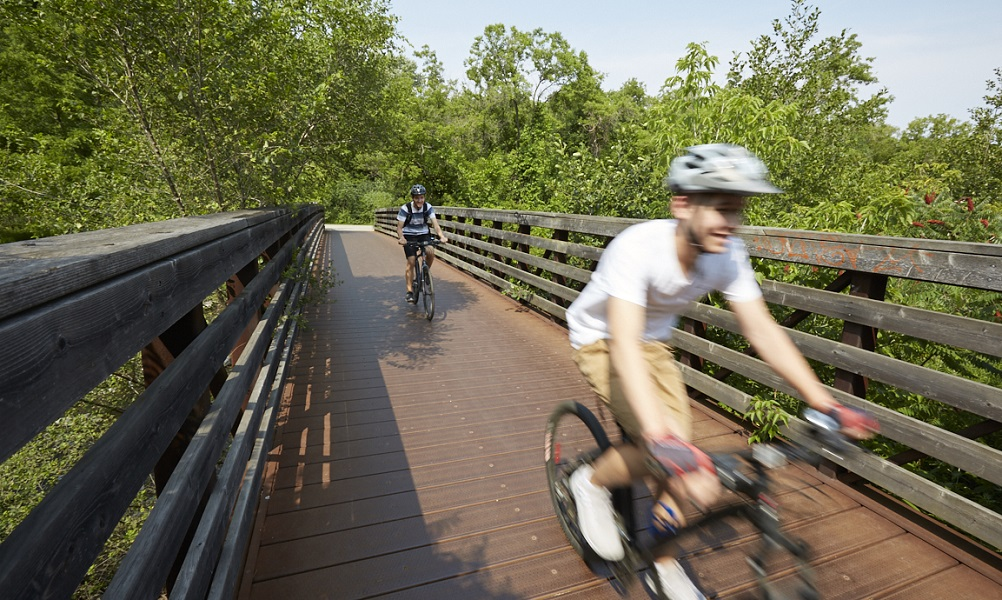 Two youth riding their bikes on a pedestrian bridge