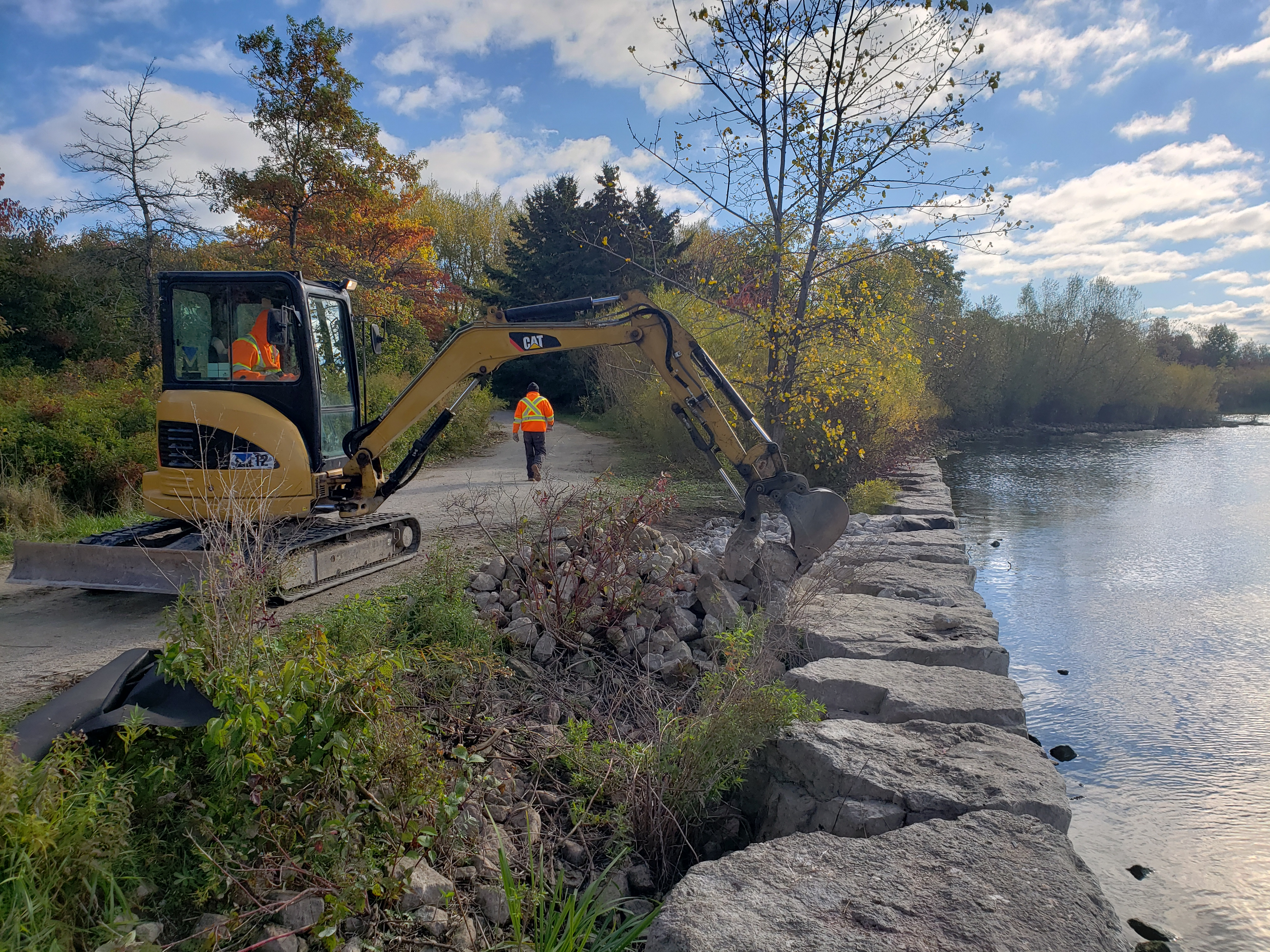 TRCA construction crews beginning to place rip rap along the backshore of the seawall at Colonel Samuel Smith Park. Source: TRCA, 2019.