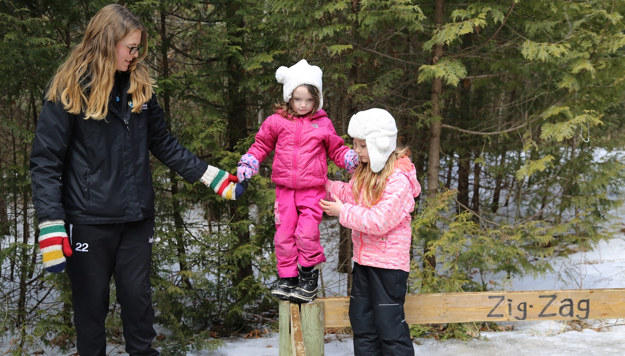 teacher and young girls practice wilderness survival activities during March Break camp at Claremont Nature Centre