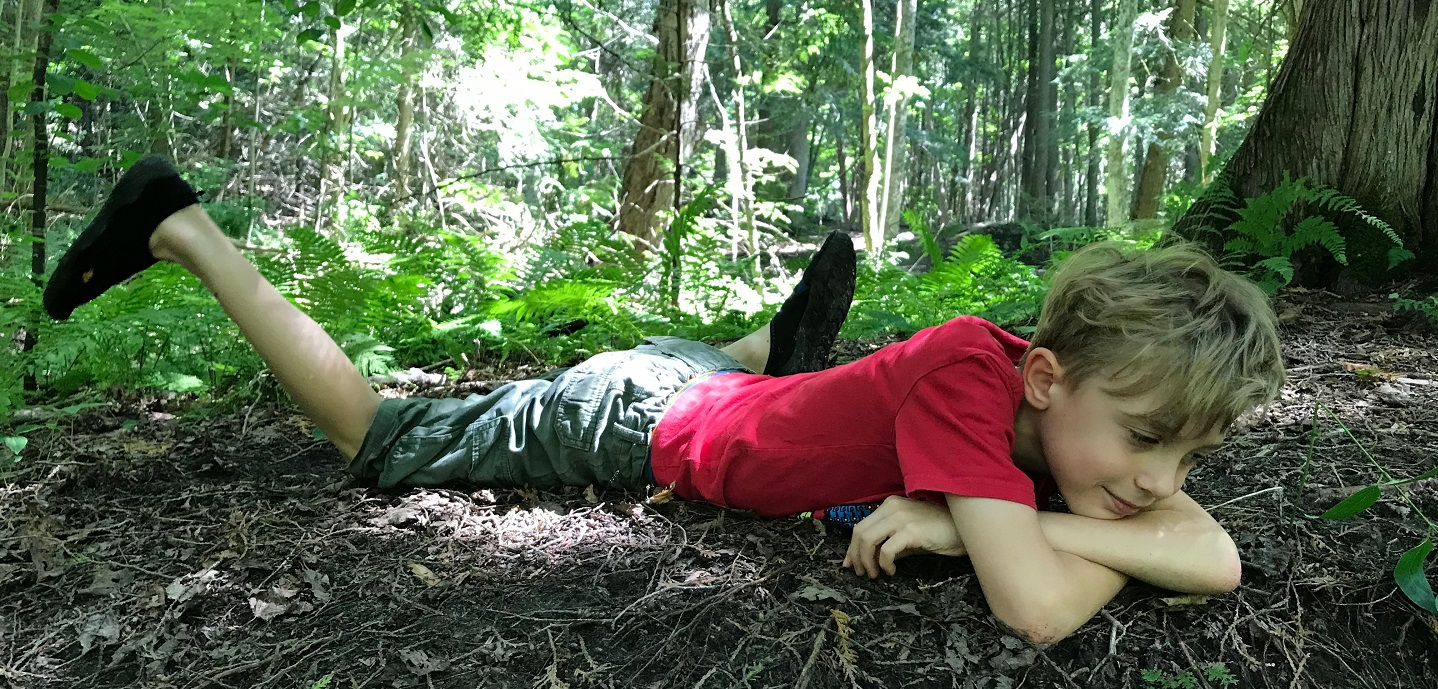 young boy resting on forest floor at Claremont summer nature day camp