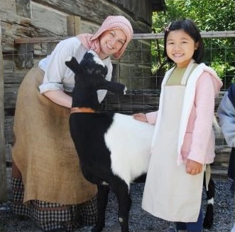 girl in period costume meets heritage breed farm animals at Black Creek Village