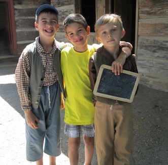 three boys visit one-room schoolhouse at Black Creek Village