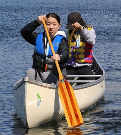 girls paddling canoe on Lake St George