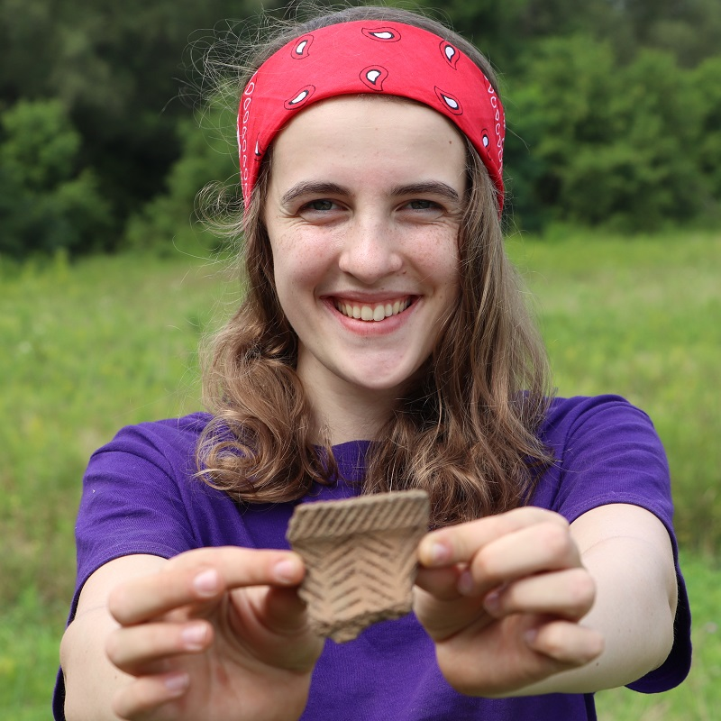 Boyd Archaeological Field School student displays artifact at dig site