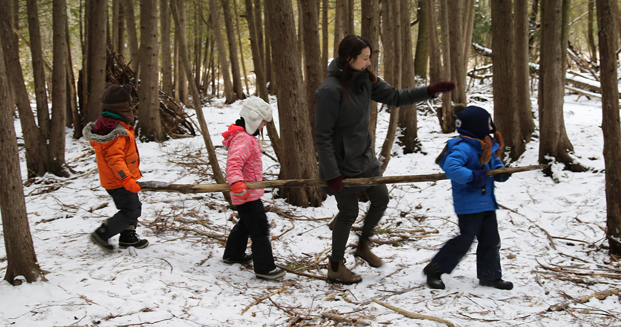 children and teacher gather wood at TRCA march break nature camp