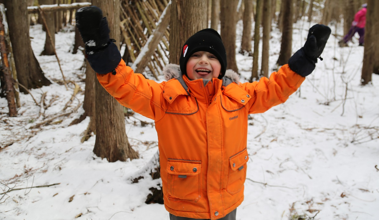 young boy playing in the woods at Lake St George march break nature camp