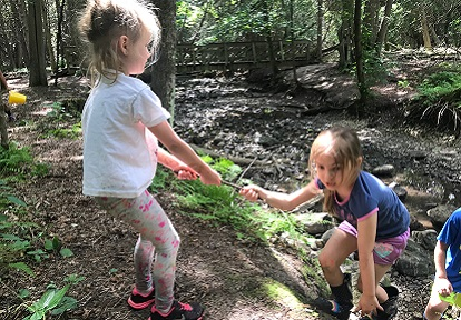 campers play in woods at Lake St George summer nature camp