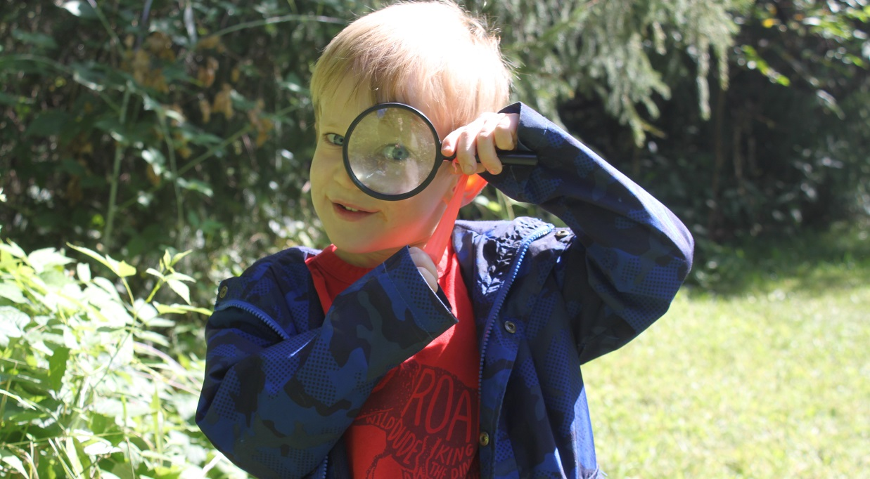 boy looks through magnifying glass during PA day camp at Claremont Nature Centre