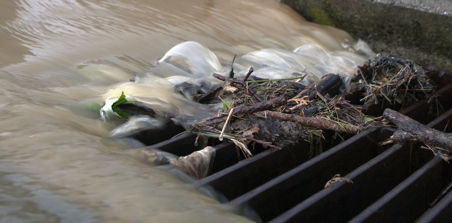 image of stormwater and debris rushing into sewer grate illustrates the focus of the rain to runoff program