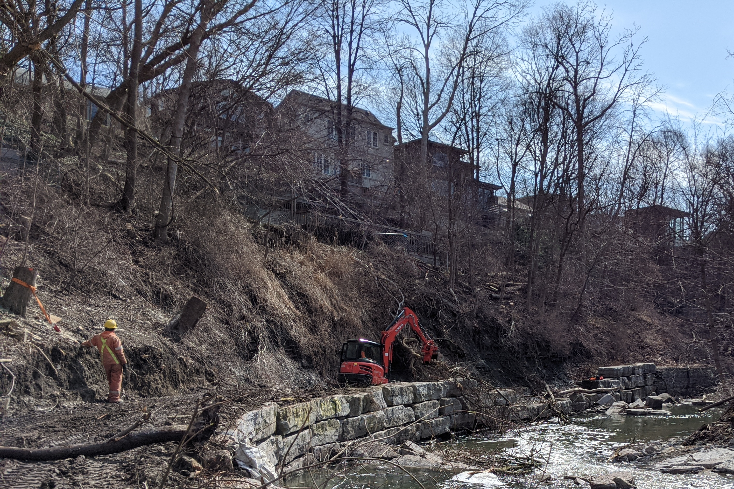 Workers removing felled trees from a construction site alongside Mimico Creek