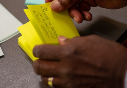resident adds post-it notes to display at Thornhill SNAP community engagement event