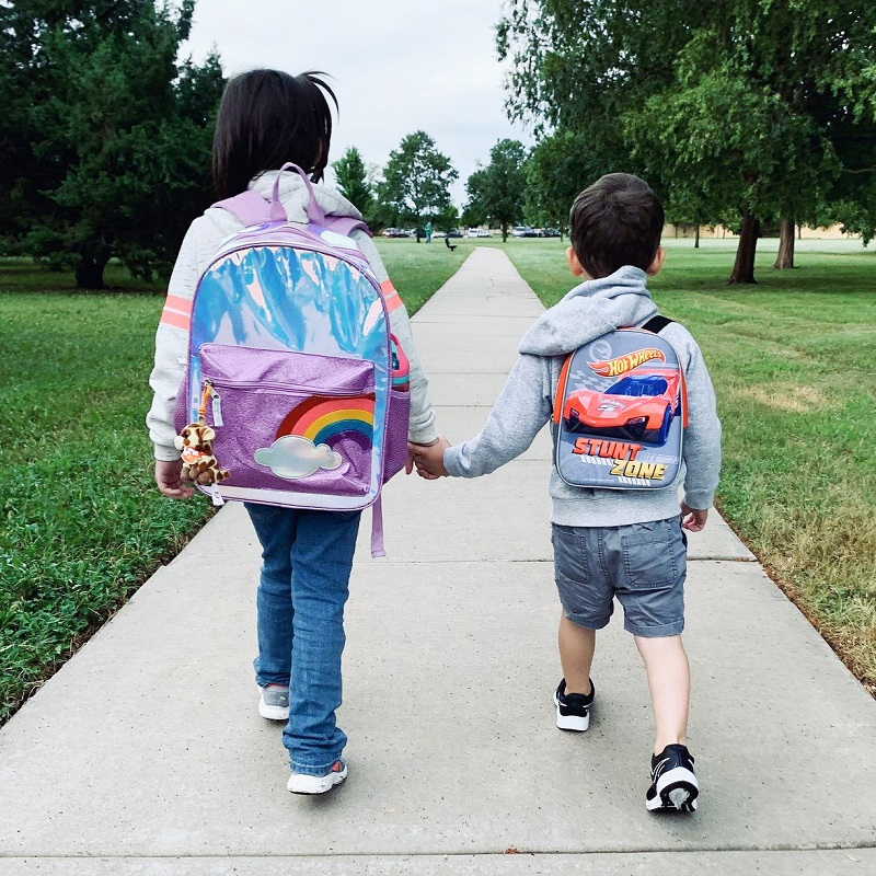 two children wearing knapsacks and walking hand in hand to school