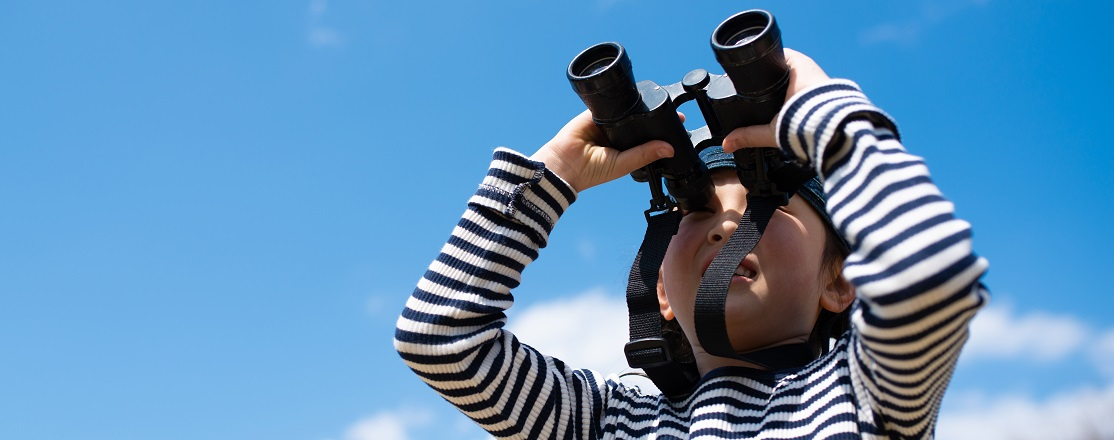 young boy looks through binoculars while participating in TRCA outdoor family fall fun experience