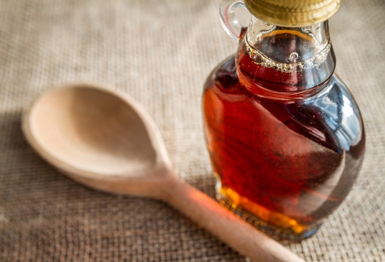 Maples syrup and wooden spoon