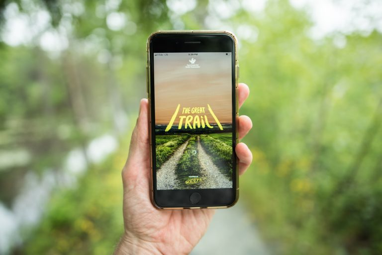 A person uses The Great Trail app on a trail surrounded by green trees in Nova Scotia.